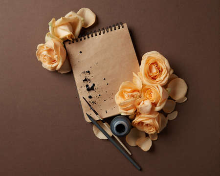 lay forward: Diary or notebook with yellow roses around for ideas and expressing emotions. Blank copy space for writing congratulations., flat lay Stock Photo