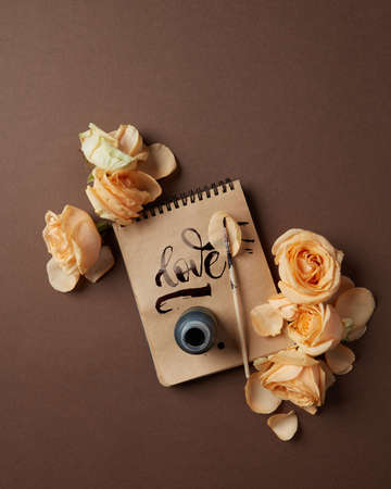 lay forward: Notepad with written word Love and flowers on a brown background, flat lay