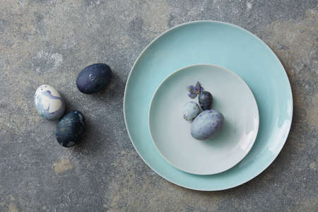blue petals: Blue easter eggs with dried petals on stone background