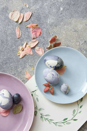 blue petals: Blue easter eggs with dried petals and watercolor frame on stone background