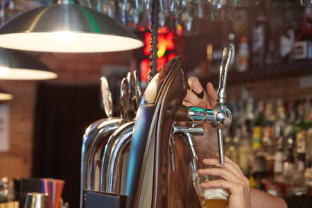 Barman pouring beer Stock Photo