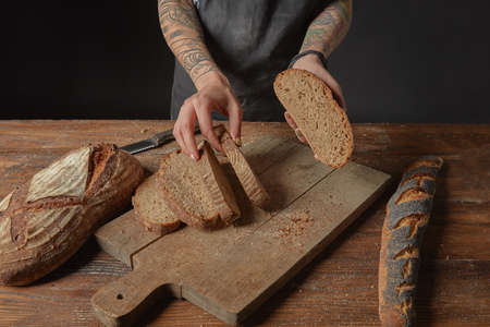 Woman with tattoos on her hands slicing grain bread on a wooden board