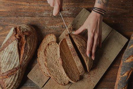 Baker Slicing Bran Bread on a Cutting Board Flat lay