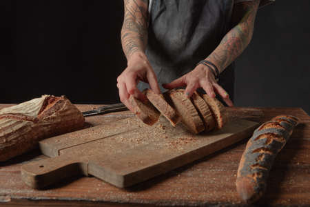 artisan bakery: Woman baker with tattoos on her hands, sliced bread from bran on a wooden table