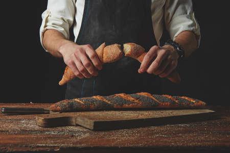 artisan bakery: Hand breaks baguette