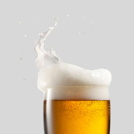 Close-up of cold beer with foam and splash on a gray background