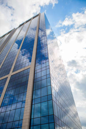 premises: clouds reflection on highrise glass building against sky