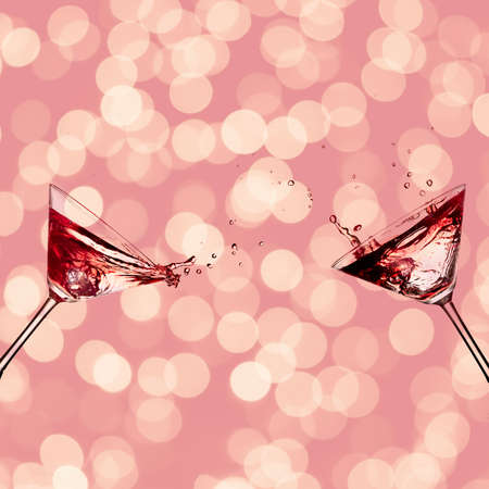 Two glasses with cocktail for martini with splash on a pink background bokeh