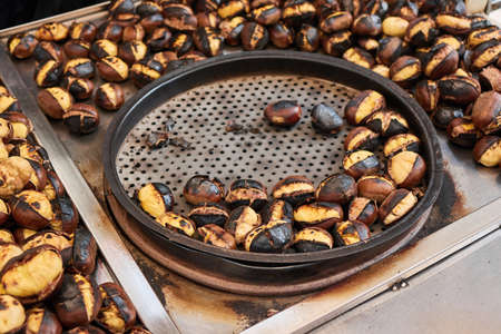 Fried chestnuts on the street. Street food. Roasted chestnuts served in a special perforated chestnut pan. Stock Photo