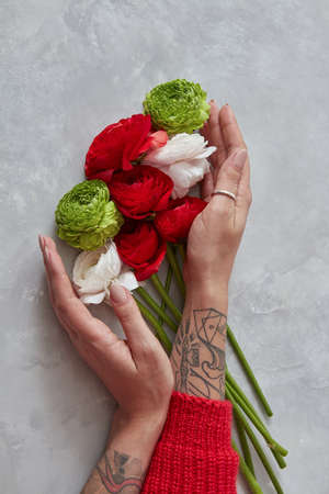 a girl holding a bouquet of white, red and green flowers on a gray concrete background. The concept of a holiday card