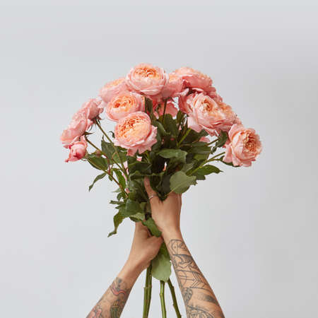 the girl is holding a bouquet of fresh pink roses, Stockfoto
