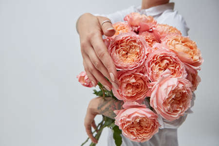 Bouquet of pink media flowers, in the hands of a girl with a tattoo bouquet of roses, mothers day, valentines day
