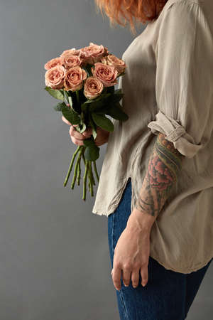 Girl holds a bouquet of beige roses cappuccino
