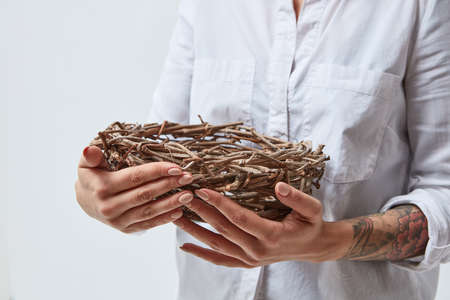 The girl is holding a nest of branches in her hands,