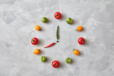 Watches made from vegetables of tomatoes and Brussels sprouts on a gray concrete background. Healthy eating. Dinner time. Top view, flat lay.