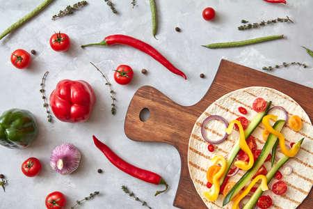 Sliced raw vegetables on a tortilla on a wooden board. The next stage of cooking burito. Step-by-step recipe. Top view, flat lay.