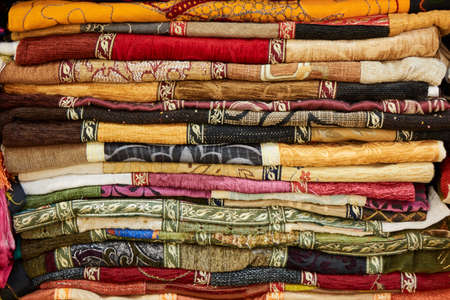 Pile of colorful folded textile. Heap of cloth fabric