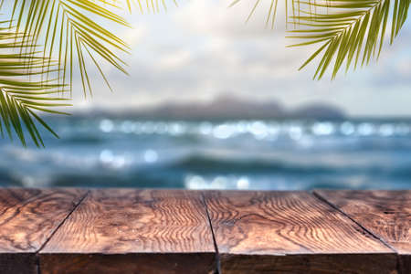 Beach blurred background with palm leaves background with vintage old wood table Foto de archivo