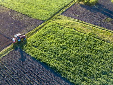 Aerial view from the drone, a birds eye view of agricultural fields with a road through and a tractor on it, in the evening, at sunset