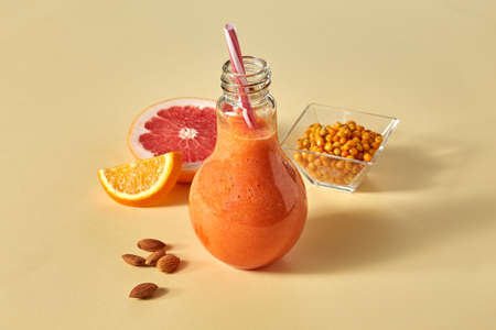 Orange smoothies with citrus, carrots, sea buckthorn and almonds on an orange paper background Stock Photo
