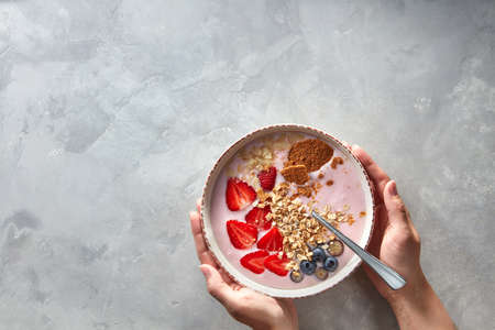 yoghurt with almond flakes, oatmeal and fresh berry served in bowl in female hands on a concrete background