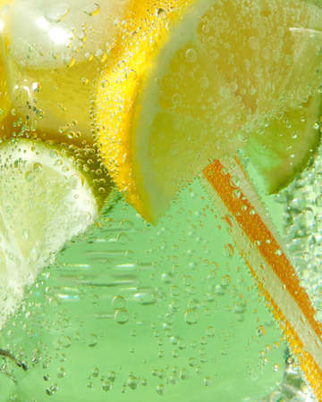 A macro shot of a glass with a cold refreshing lemonade with ice, pieces of lime, lemon and mint leaves, plastic straws on a green background. Bubbles of air in a glass jar.