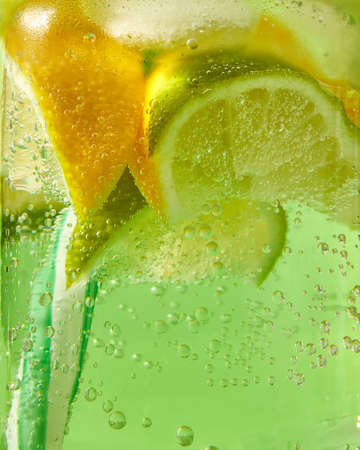 Close-up of sparkling fresh lemonade with ice, slices of lime, lemon and colored plastic straws in glass with large bubbles of air. Banco de Imagens