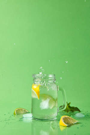 Splash and drops of lemonade from a glass and slices lime, lemon, mint sprig on a green table. Glass jar with homemade sparkling lemonade on green background with copy space.
