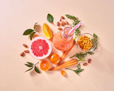 Orange smoothies from orange vegetables and fruits in a glass bottle with orange, grapefruit, carrots, nuts on a beige background. Stock fotó