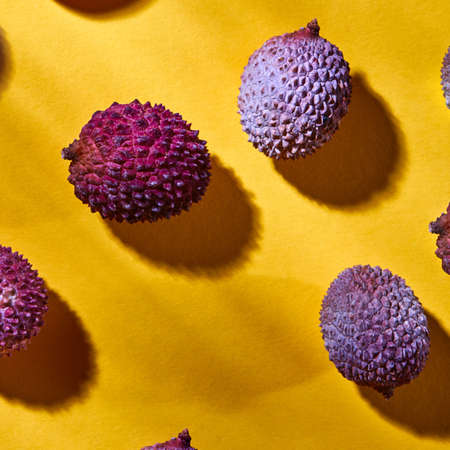 Top view of tropical litchi fruit on a yellow background with hard shadows. Foto de archivo