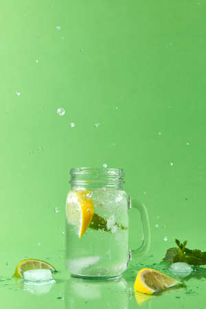 Splash lemonade in different directions from a mason jar with natural lemonade handmade. Drops of liquid and pieces of lemon and lime on a green table with place for text.
