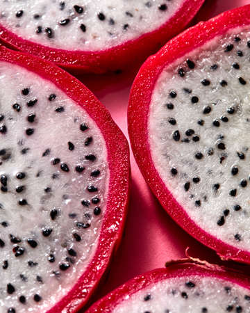Close up view of background from round slices of Dragon fruit or Pitaya on a pink background.