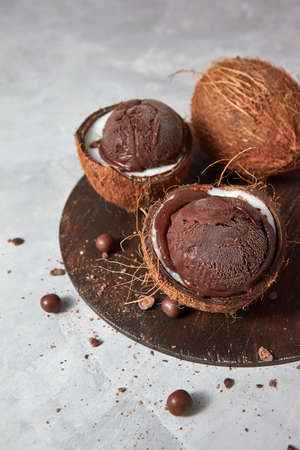 Fresh appetizing chocolate ice cream in a coconut shell with chocolate balls on a wooden board on a gray.