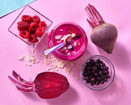 Healthy smoothies cooked from beets, raspberries, black currants and almond flakes on a duotone blue pink paper background. 写真素材