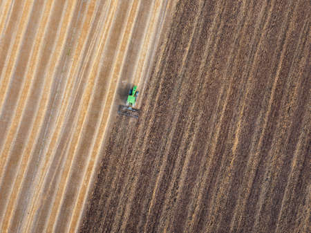 Agricultural field after harvesting and part of the field plowed of tractor under sowing works .
