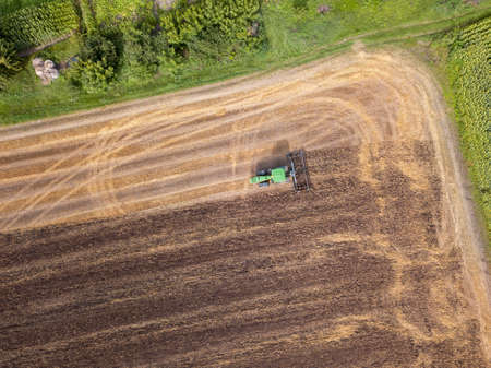 Plowing the ground after harvesting on the field in the autumn time. Top view. Stock Photo
