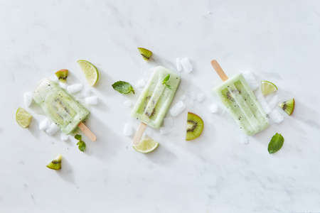 Sticks of ice cream with kiwi and lime on a gray marble background with pieces of ice and mint leaves. Copy space. Flat lay