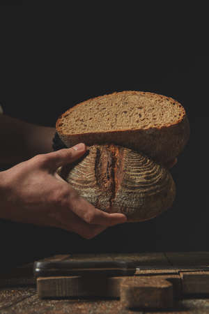 Close-up a male baker holding in his hands halves of fresh rye bread, against the background of an old brown table 版權商用圖片