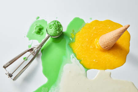Multicolored splashes of melted ice cream. Scoop of green ice cream and a fallen waffle cone with a yellow ice cream on a blunder background with a copy of the space.Top view Stock Photo