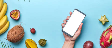 Coconut, lychee, pineapple set of tropical fruits. The girls hand is holding the phone on a blue background with a copy of the space. The concept of modern online shopping. Flat lay
