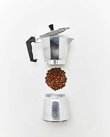 Metal coffee maker and a pattern of coffee beans in the shape of a circle on a gray background with copy space for text. Making coffee. Flat lay