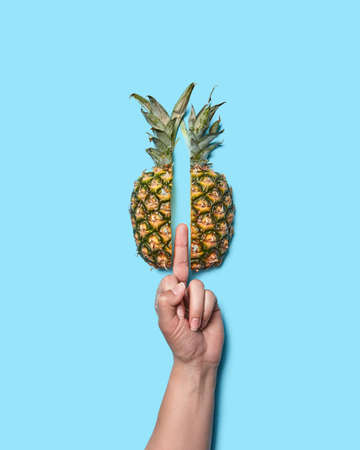 A sign with a womans hand fucking and a half pineapple on a blue background with space for text. Flat lay