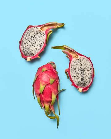 Two halves and a whole tropical fruit pitahaya presented on a blue background with copy space. Food layout. Flat lay