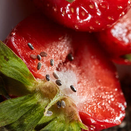 Close up of half of red ripe strawberry with seeds as a background.