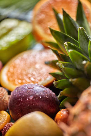 Tropical fresh background with exotic Passion fruit in a droplets of water and green pineapple leaves. Sallow depth of field.