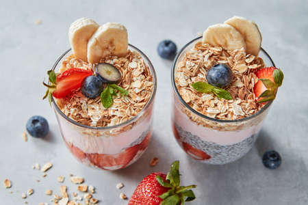 Dietary natural breakfast with natural organic ingredients - strawberries, granola, banana in a glass on a wooden table. Healthy vegetarian eating.