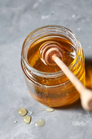 Wooden stick in a glass jar with fresh natural organic honey on a gray concrete table. Jewish New Year healthy holiday.