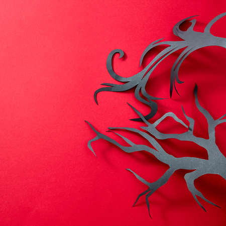 Handcraft black tree from paper on a red background with reflection of shadows and copy space for text. Creative Halloween layout. Flat lay
