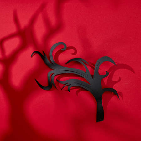 On a red background scary shadows and handcraft paper branches with copy space for text. Halloween card. Flat lay
