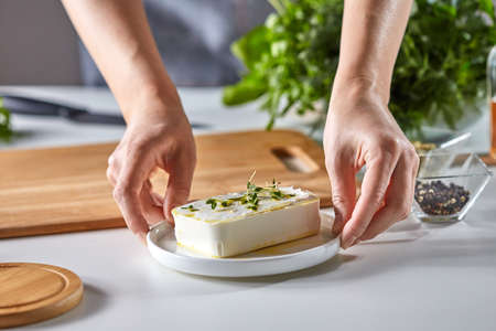 The girl's hands are holding organic cheese, with healthy green sprouts in a plate on the kitchen table with fresh greens and copy space.
